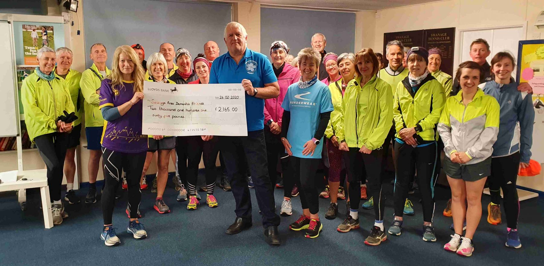 Purbeck Runners Chair Paula Lawton-Archer presenting the cheque to Charity Chair and Swanage Mayor Mike Bonfield with members of the Purbeck Runners